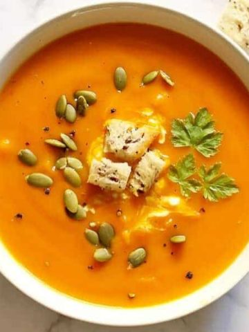 a bowl of roasted pumpkin, sweet potato and carrot soup topped with croutons and pepitas