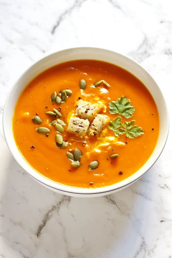 roasted pumpkin and sweet potato soup in a white bowl topped with seeds and croutons