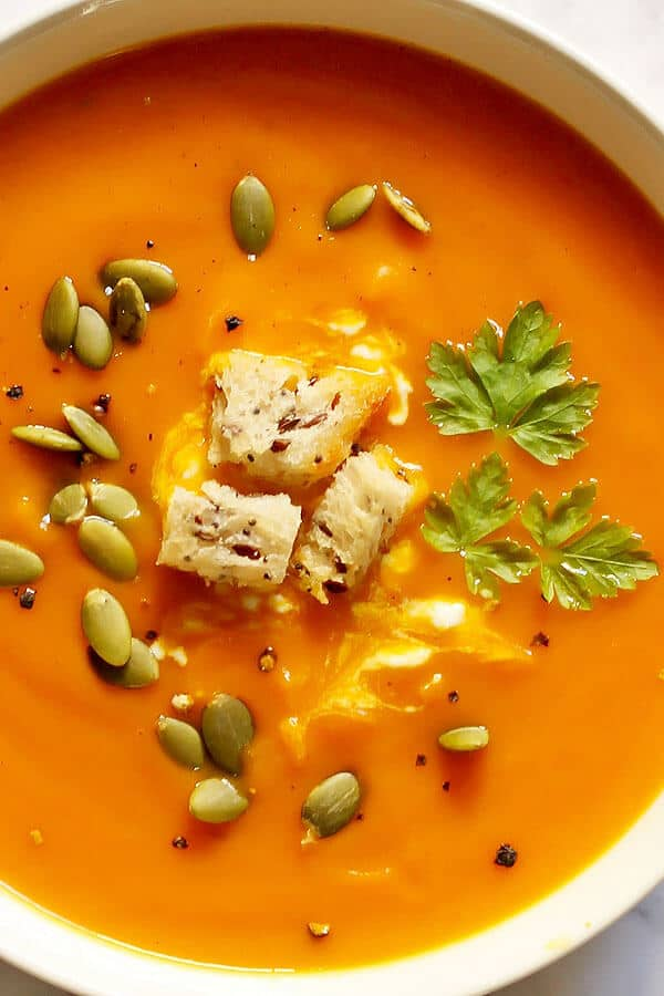 close up of a bowl of roasted pumpkin and sweet potato soup topped with seeds and croutons