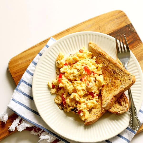 Easy scrambled eggs with veggies and two pieces of toast on a white plate