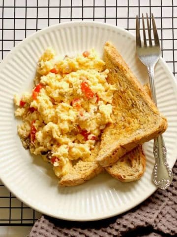 Pizza-style scrambled eggs and two pieces of toast on a white plate