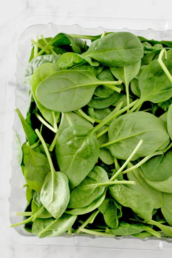 loose spinach leaves in a plastic container