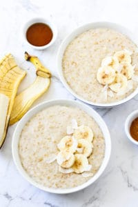 two bowls of steel cut oats topped with banana slices
