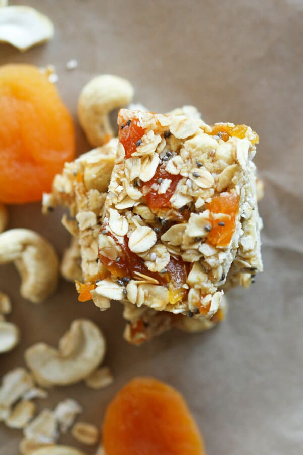 chewy apricot muesli bars stacked on top of each other with cashews and apricots scattered around