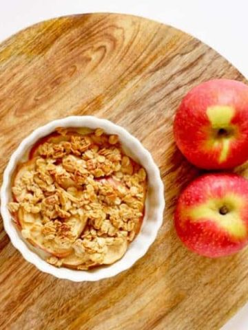 apple crisp sitting on wooden cutting board next to two red apples