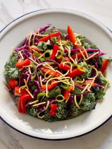 crunchy kale salad with lemon tamari dressing on a white plate