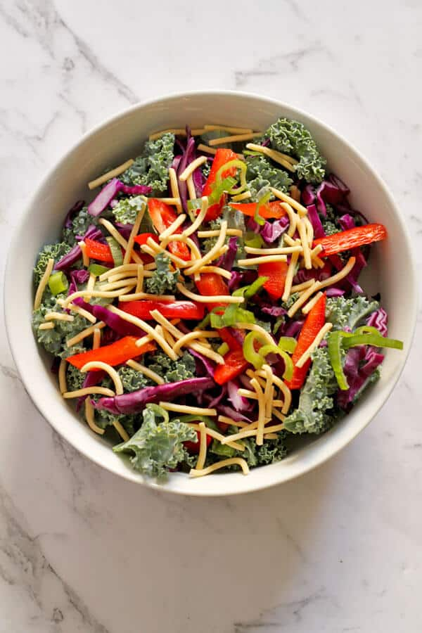 crunchy kale salad with lemon tamari dressing in a white bowl