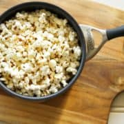 a saucepan filled with popcorn sitting atop a wooden cutting board
