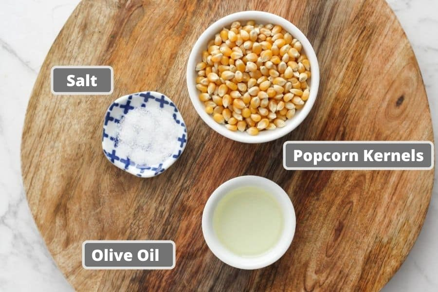 stovetop popcorn ingredients on a wooden board.