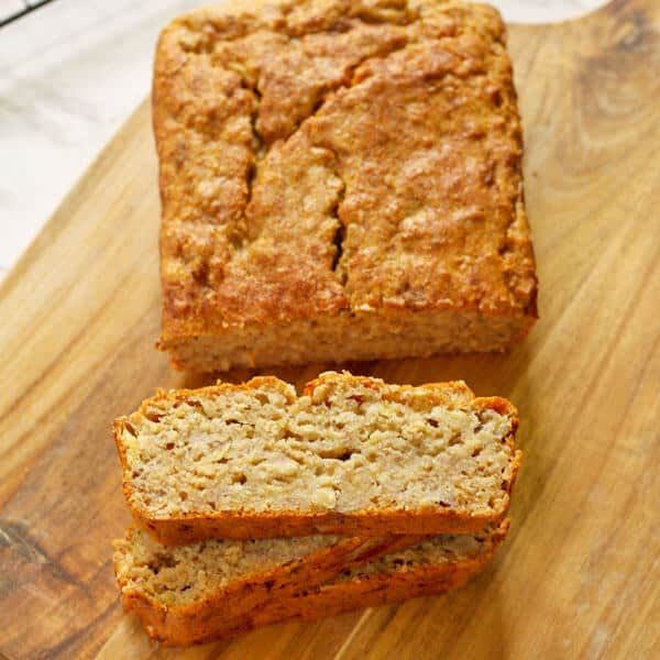 slices of healthy banana bread stacked on top of each other with the loaf sitting behind