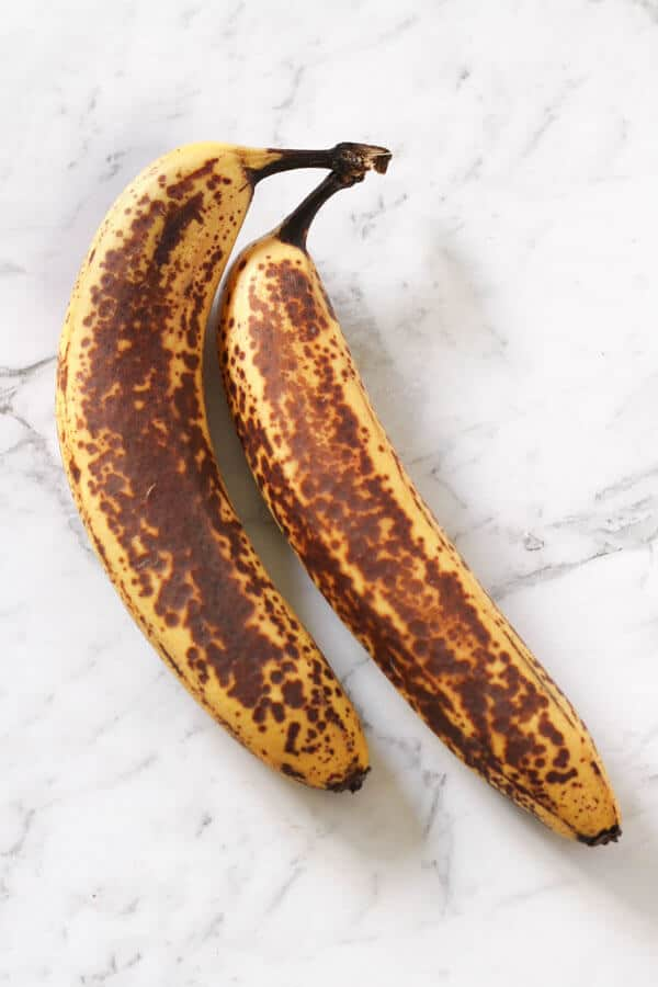 two spotty bananas on a white marble background