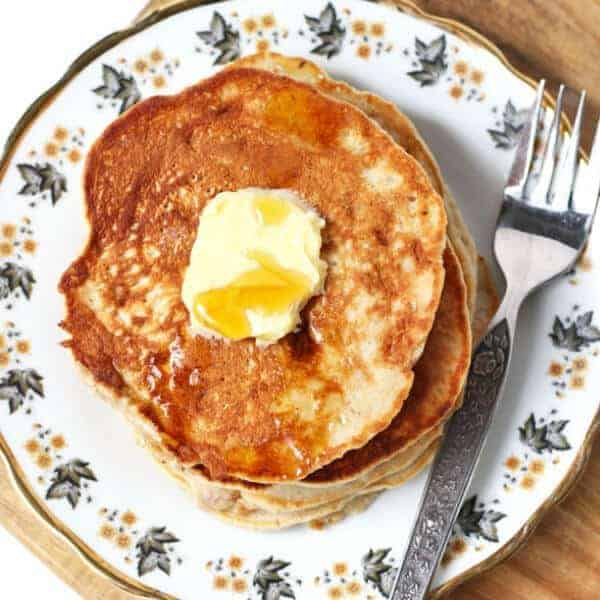healthy banana pancakes stacked on a pattered plate with butter and maple syrup on top