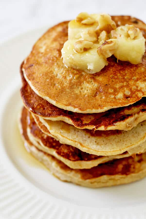 healthy banana pancakes stacked on a white plate with caramelised banana slices and pecans on top