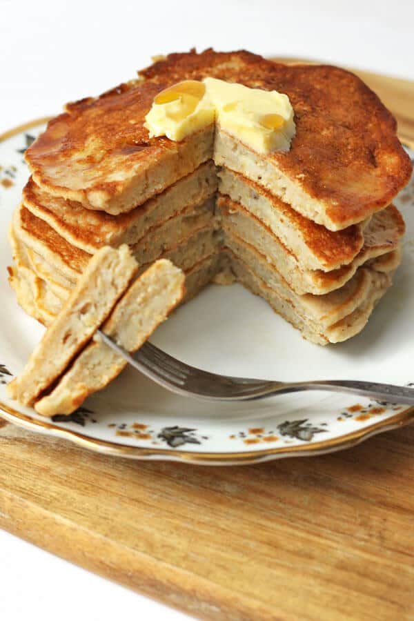 healthy banana pancakes layered on a patterned plate with a wedge sliced off to show the inside of the pancakes