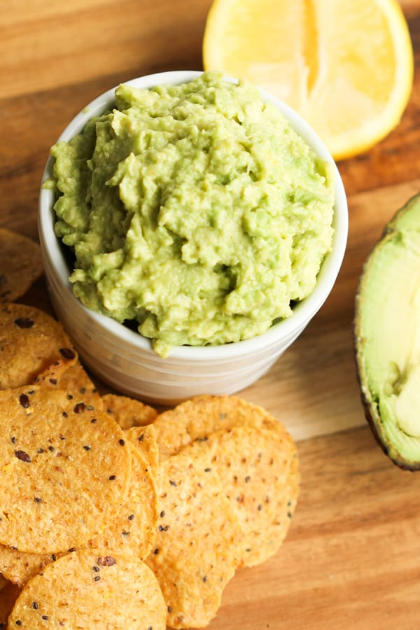 guacamole in a white bowl surrounded by corn chips, avocado and lemon wedges