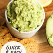 "guacamole in a white bowl surrounded by corn chips with text overlay ""quick & easy guacamole"""