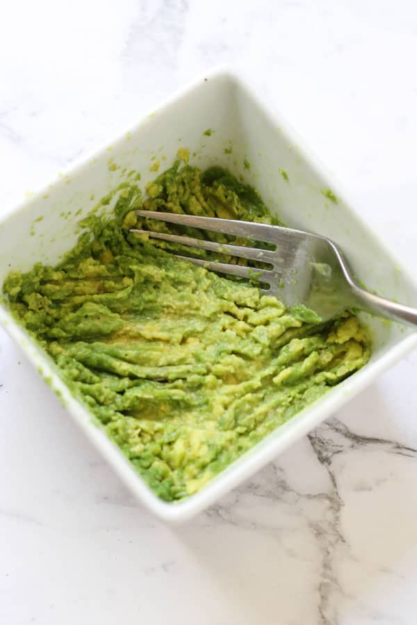 a fork pressing into mashed avocado in a white bowl