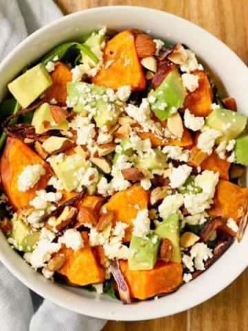roasted sweet potato, avocado and feta salad in a white bowl on top of a wooden cutting board