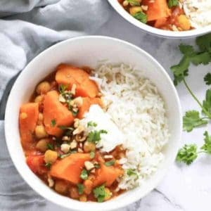 sweet potato, lentil and chickpea curry in a white bowl topped with coriander and crushed peanuts