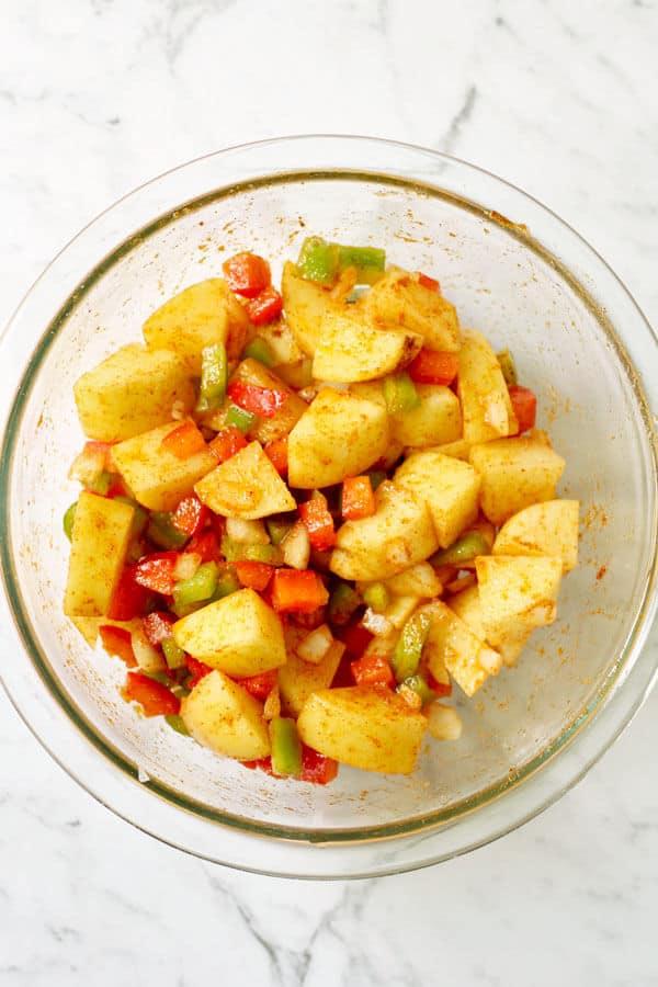 crispy breakfast potatoes ingredients in a glass bowl