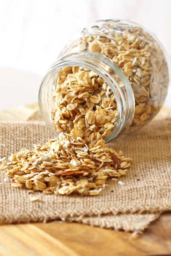 a glass jar of healthy homemade granola thats tipped on its side with granola spilling out