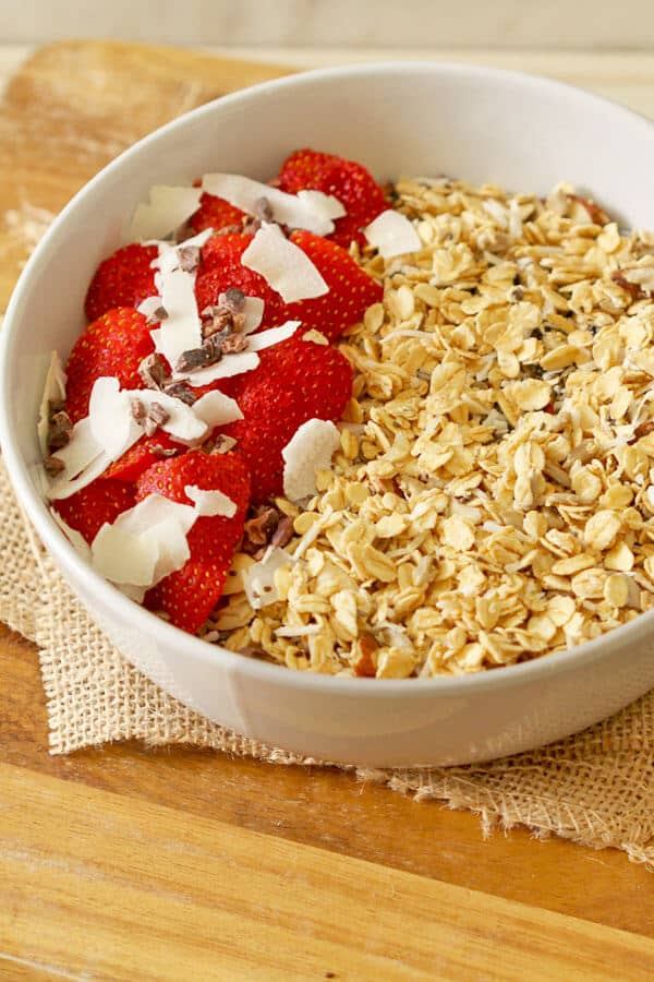 healthy homemade granola in a bowl with cut up strawberries and coconut flakes on top