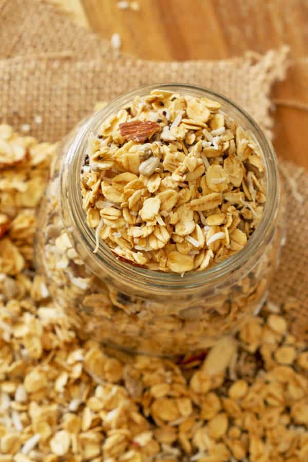 healthy homemade granola in a glass jar sitting on top of a pile of loose granola
