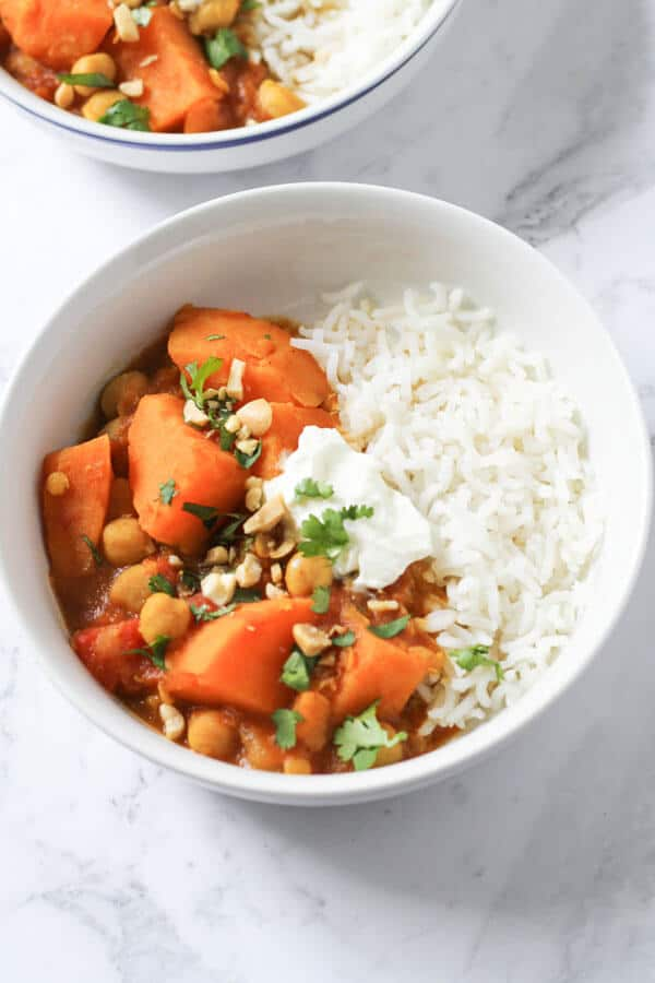 a bowl of sweet potato, lentil & chickpea curry topped with coriander, yoghurt and crushed peanuts