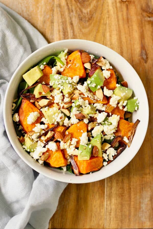 sweet potato, avocado and feta salad in a white bowl on a wooden cutting board
