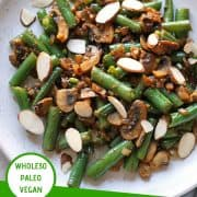 """sauteed green beans and mushrooms on a white plate with a text overlay that reads """"sauteed green beans & mushrooms - whole30, paleo & vegan"""""""