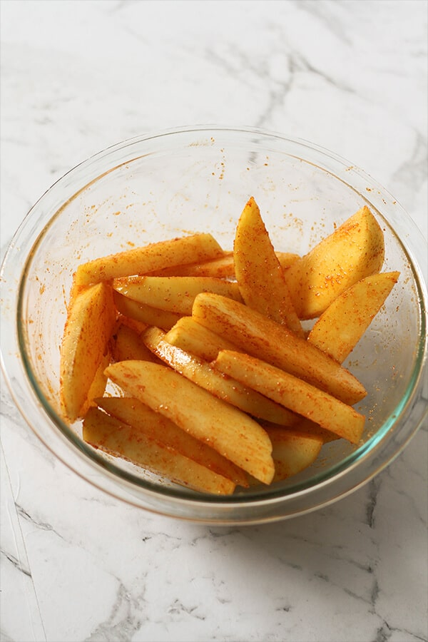 potato wedges in a glass bowl covered in seasoning.