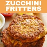 carrot and zucchini fritters stacked on a wooden board.