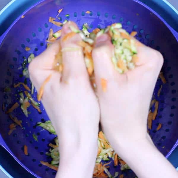 hands squeezing shredded carrot and zucchini