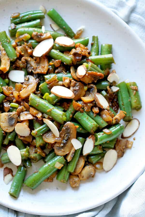 sautéed green beans and mushrooms on a white plate