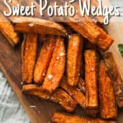 "sweet potato wedges covered in salt on a wooden serving board with text overlay ""air fryer sweet potato wedges""."