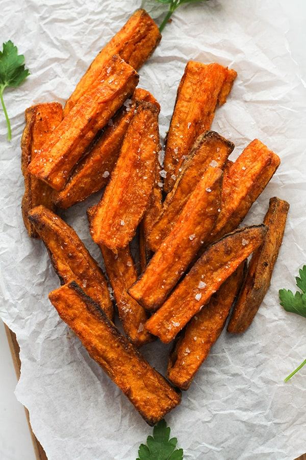 sweet potato wedges on white baking paper covered in salt.