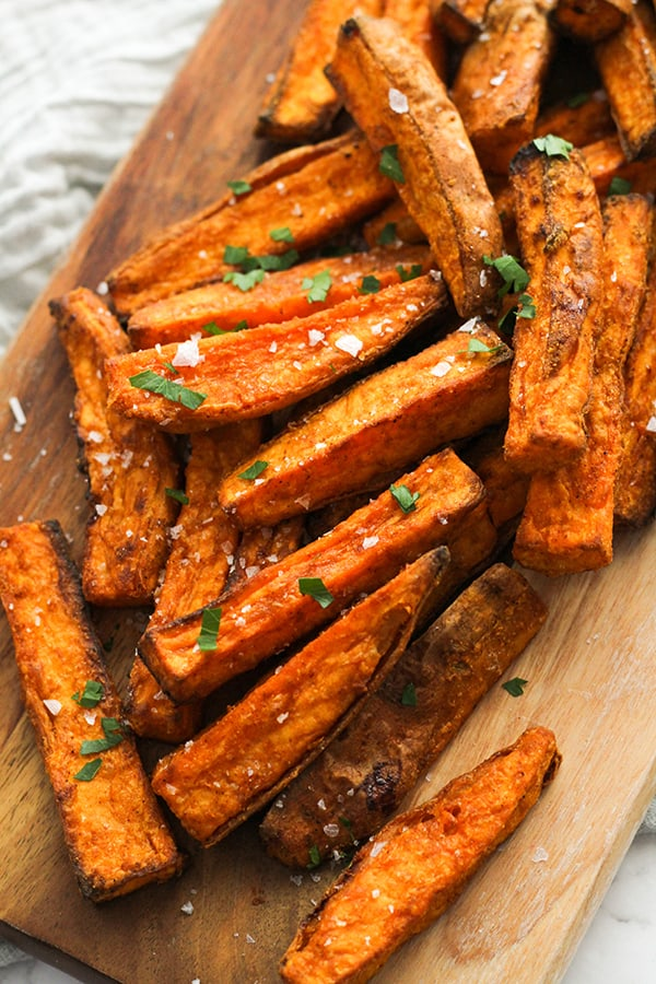 sweet potato wedges covered in salt on a wooden serving bowl.