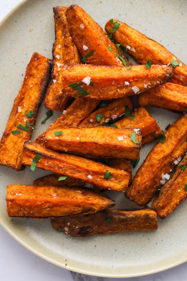 sweet potato wedges covered in salt on a white plate..