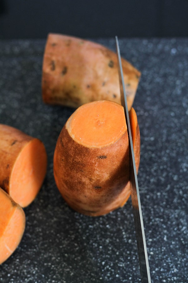 a knife slicing the edge off a sweet potato