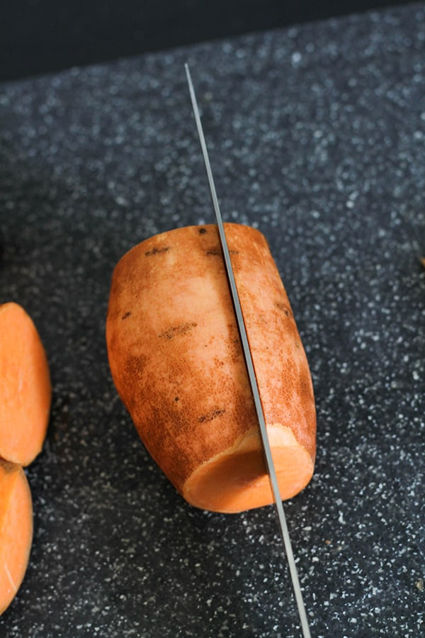 a knife slicing a sweet potato into thirds.