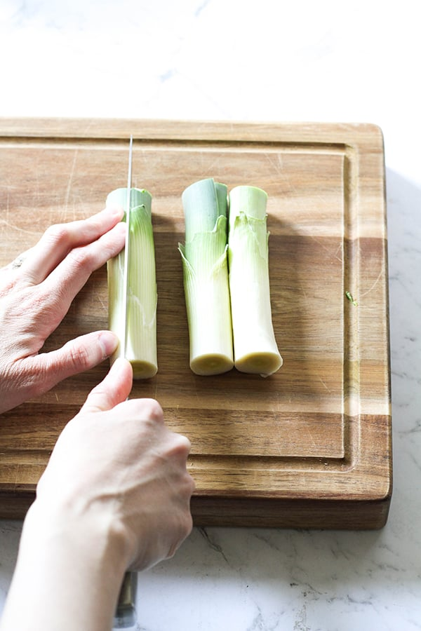 Leeks on a wooden chopping board with a hand slicing the leeks in half.