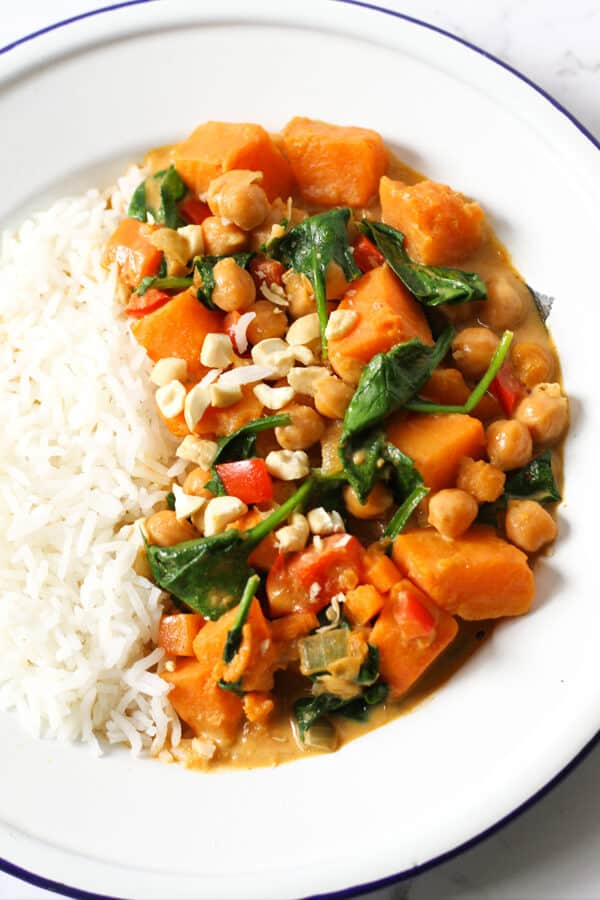 close up of sweet potato, chickpea and spinach curry in a bowl with rice