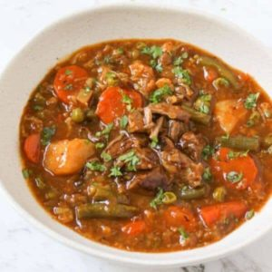 beef and vegetable stew in a white bowl