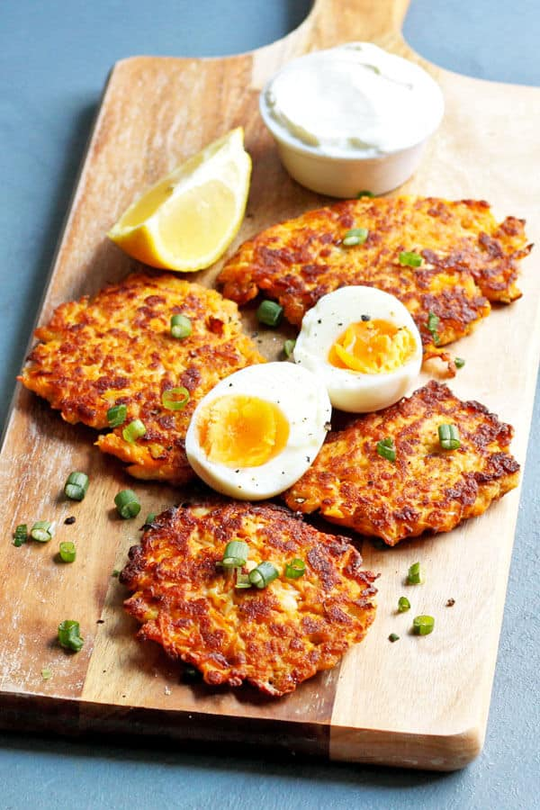 sweet potato rosti laid on top of wooden cutting board with eggs