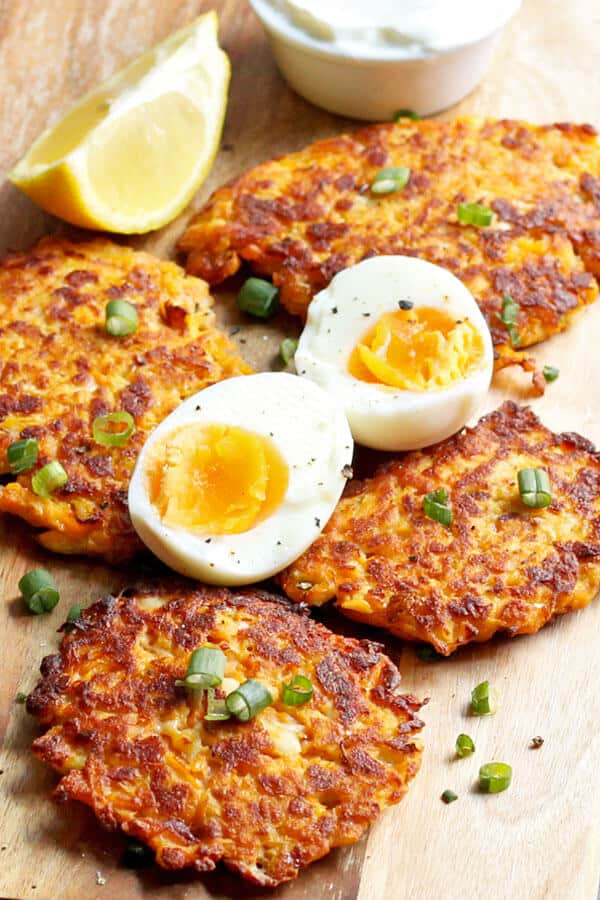 sweet potato rosti laid on a wooden cutting board with hard boiled eggs