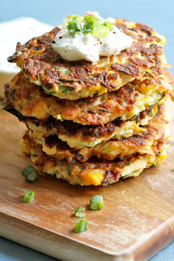 zucchini haloumi fritters on a wooden chopping board