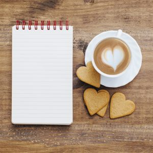 Vintage notepad with cup of coffee and love heart shaped biscuits
