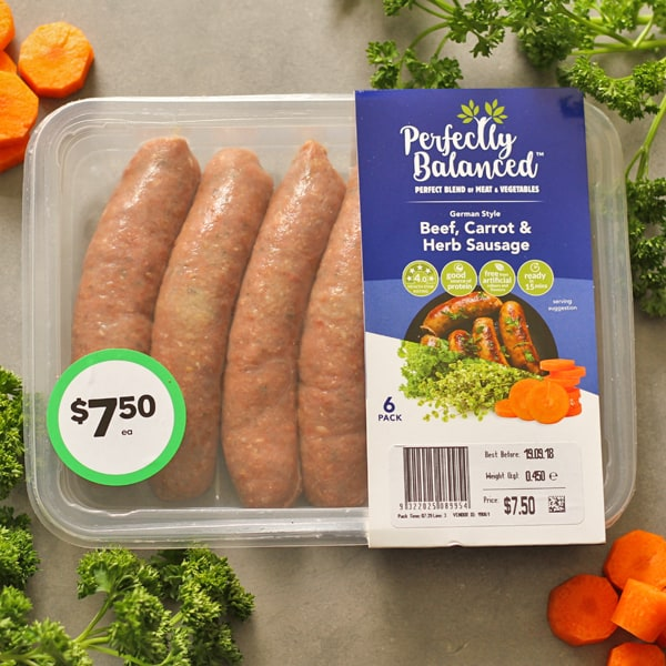 A package of Perfectly Balanced Beef, Carrot & Herb Sausages surrounded by parsley leaves and carrot slices