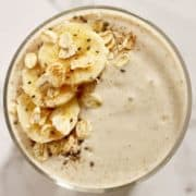 banana oat smoothie close up topped with banana slices, rolled oats, cinnamon and chia seeds