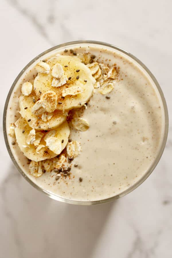 banana oat smoothie from above topped with banana slices, oats, cinnamon and chia seeds